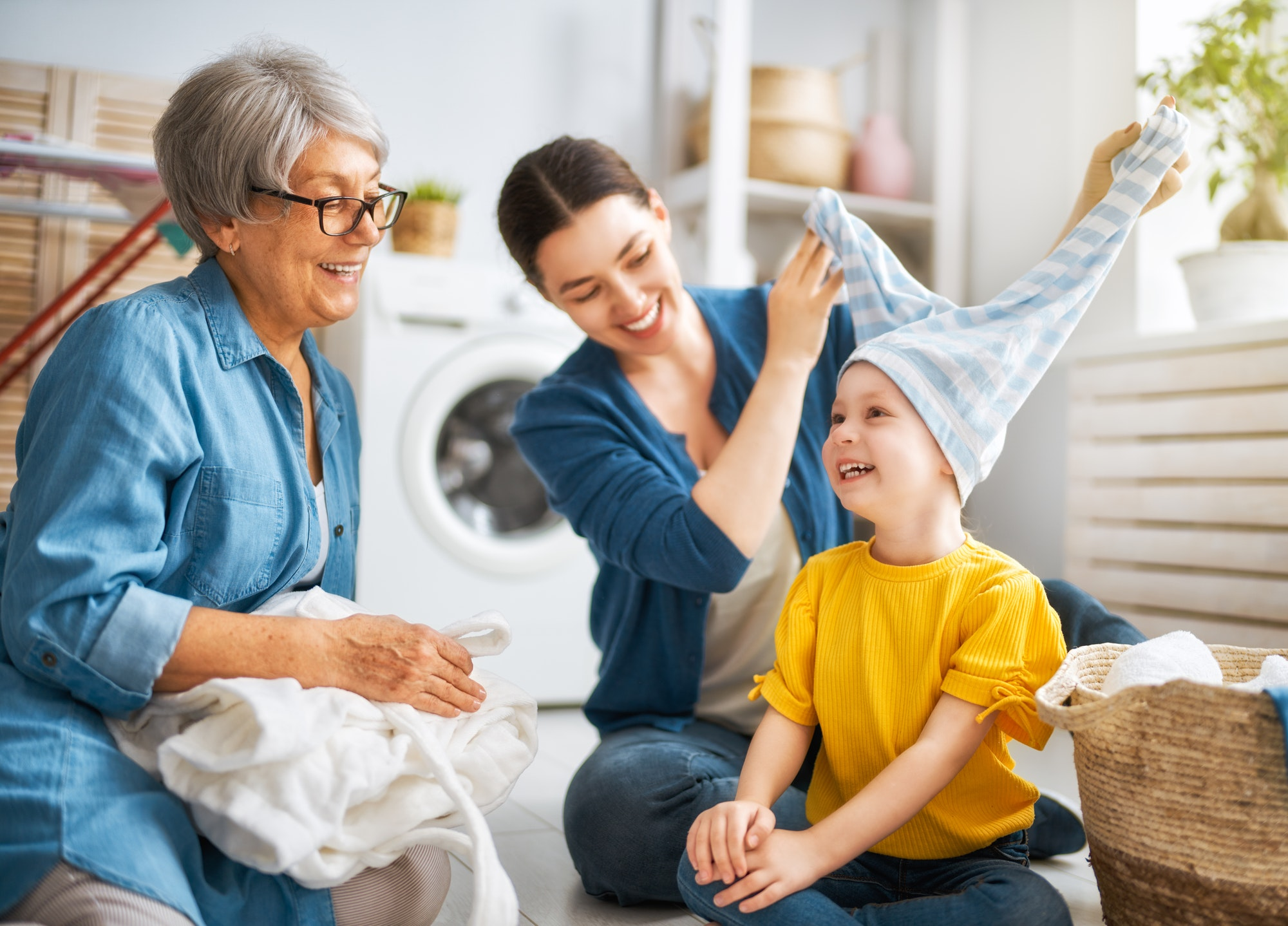grandma, mom and child are doing laundry